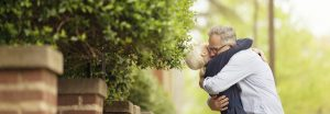 middle aged couple hugging by hedge