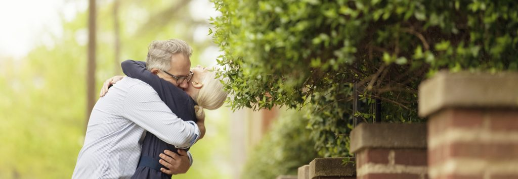 middle-aged-couple-hugging-by-hedge