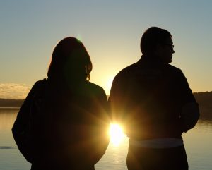 Silhouette of Couple standing staring at sunset